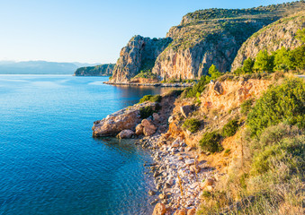 Greek coastline with rocky cliffs and pebble beaches near Nafplio town Fotobehang