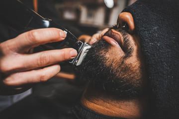 un barbero está pasando la maquina eléctrica de cortar y afeitar por la barba de un chico brasileño afroamericano. de estilo swing hipster.
