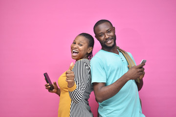two young african friends, boy and girl, looking excited while viewing something on their smartphone