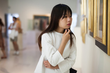 Thoughtful chinese woman standing in art museum near the painting Fototapete