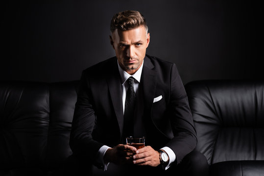 Handsome businessman with glass of whiskey looking at camera on couch isolated on black