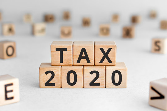 Tax 2020 - phrase from wooden blocks with letters, Tax time 2020 concept, random letters around, white  background