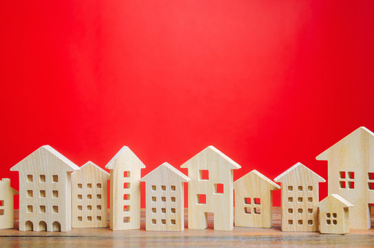 Miniature wooden houses on a red background. Real estate concept. City. Agglomeration and urbanization. Market Analytics. Demand for housing. Rising and falling home prices. Population. Copy space