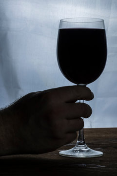 blackout hand with wineglass of red wine on a wooden table and white blurred background. Drink close up. concept problem of alcohol addiction, alcoholism dependence