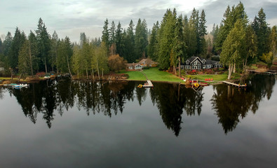 Lovely Lake Joy and the waterfront houses on a fog covered day with the surrounding trees and lingering clouds above reflecting in the water in the pacific northwest.