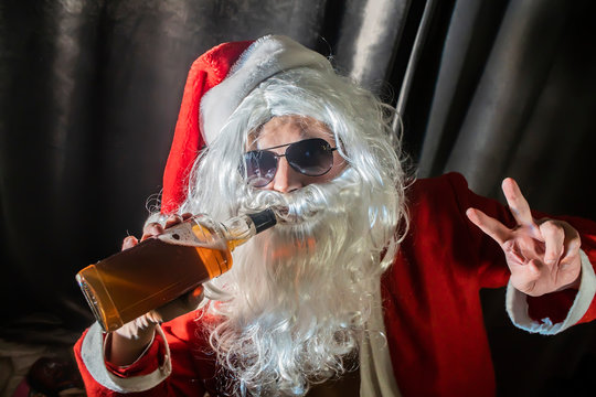 bad santa man portrait at dark room, Santa Claus with a bottle of whisky enjoying a drink