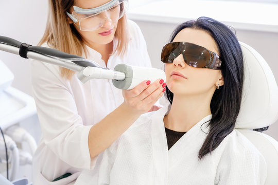 Close up beautician hand holds ultrasound machine and cleans face of client girl in safety glasses from age spot and acne. Concept clean and healthy skin. Laser peeling procedure in cosmetology clinic