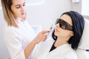 Charming woman beautician in white uniform doing laser face cleaning for young woman in safety glasses sitting in light beauty parlor modern medical clinic. Concept of elasticity and skin restoration