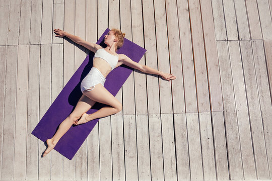 Top view. Beautiful young woman in white sportswear doing yoga outdoor on purple mat, wooden terrace. Yogi Girl lying in Belly Twist Pose, Jathara Parivartanasana. Sport and healthy life concept