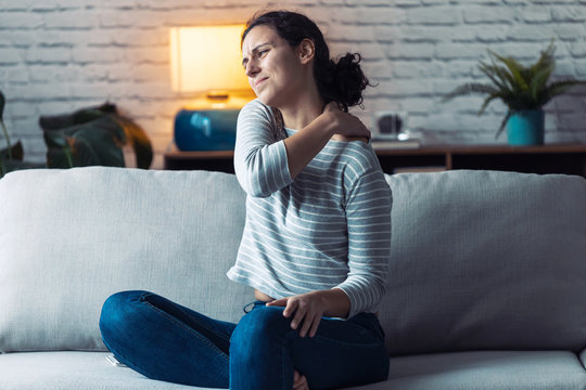 Young woman with back pain sitting on the sofa in the living room at home.