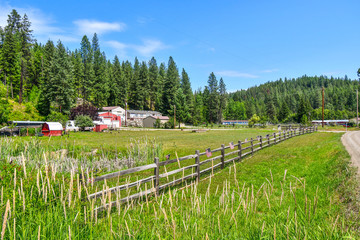 A small roadside home site farm on acreage flies American Flags along their picket fence on July 4th in the Coeur d'Alene area of North Idaho, USA