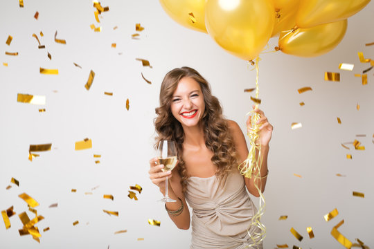 attractive young stylish woman celebrating new year, drinking champagne holding air balloons, golden confetti flying, smiling happy, white background, isolated, wearing party dress