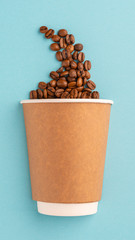 Paper recyclable Cup with scattered coffee beans on a blue paper background