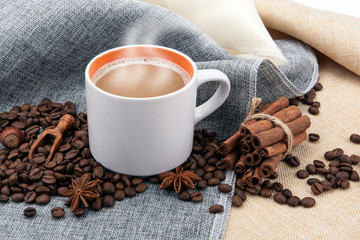 Wall Mural - cup of milk coffee on colored cloth and roasted coffee beans close up