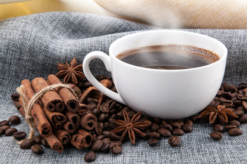Wall Mural - cup of black coffee on colored cloth and roasted coffee beans close up
