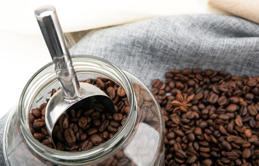 Wall Mural - roasted coffee beans with scoop in the glass jar on a bag