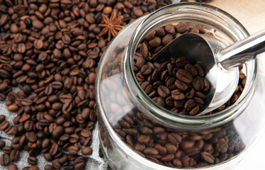 Wall Mural - roasted coffee beans with scoop in the glass jar