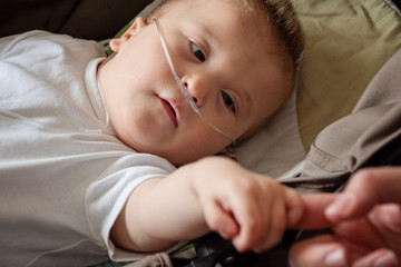 Baby boy with cerebral palsy is getting oxygen. Nasal catheter in a child patient in hospital. Respiratory support. Child on oxygen therapy holding mother's hand.