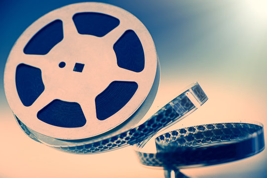 Aluminum reel with 16mm film on a colored background, close-up.
