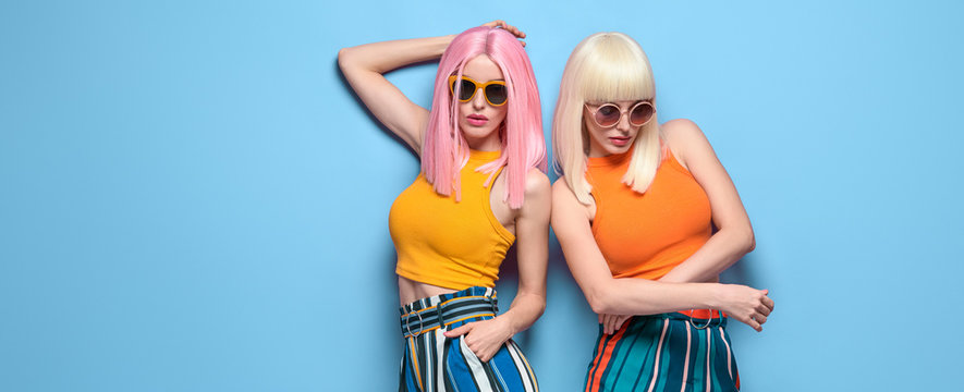 Two Young carefree Woman in stylish sunglasses, striped pants. Beautiful fashionable model girl in trendy summer outfit. Graceful friends with fashion dyed hairstyle, make up on blue. Creative banner
