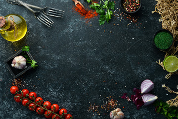 Fotomurales - Food banner. Spices, vegetables and herbs on a black stone background. Top view. free space for your text. Rustic style.