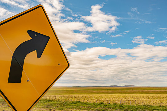 right turn sign with a green field in the background and sky with clouds