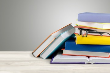 Wall Mural - Stack of books and eyeglasses on wooden background