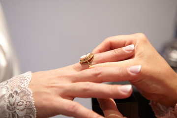 Woman putting on a ring. Closeup picture