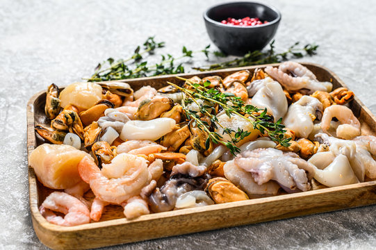 Raw sea seafood cocktail in a wooden bowl. Gray background. Top view
