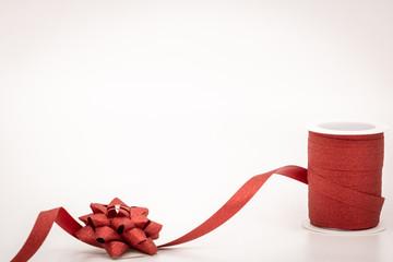 Bobine de bolduc rouge à paillettes déroulée pour faire les cadeaux de noël avec le nœud en bolduc assorti photo studio sur fond blanc avec espace texte