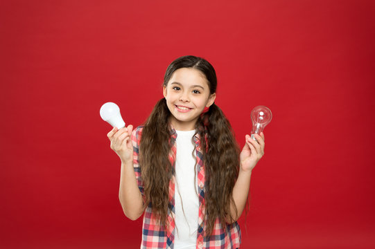 Eco life. Lighting choice. Little girl light bulbs on red background. Symbol of idea progress and innovation. Environment friendly lighting. Energy efficient lighting. Ecology problem. Climate change