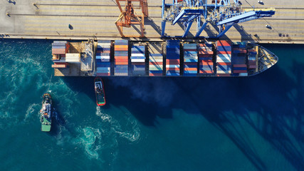 Aerial drone top down photo of industrial cargo container tanker ship carrier docked in commercial port terminal Wall mural