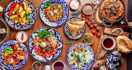 Traditional Uzbek oriental cuisine. Uzbek family table from different dishes for the New Year holiday. The background image is a top view.