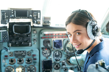 Happy and successful flight. Smiling female pilot in the aircraft , she is holding aviator headset and looking at camera. Wishes a successful fligh. Wall mural