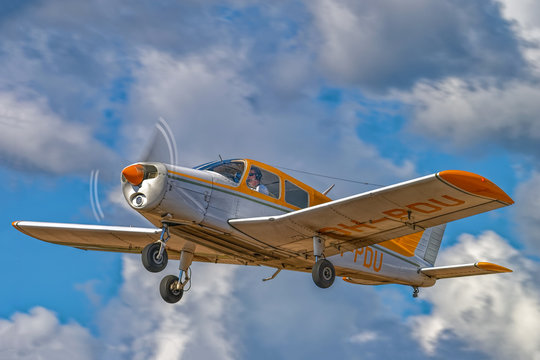Four-seat light all-metal single-engined piston-powered airplane Piper PA-28-140 Cherokee Cruiser OH-PDU flying in a blue sky against a background of white clouds. Kotka, Finland.