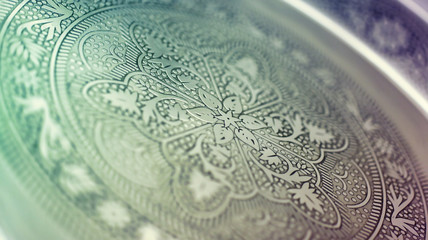 macro closeup on a handicraft classic metallic tray with Arabia or Islamic art pattern
