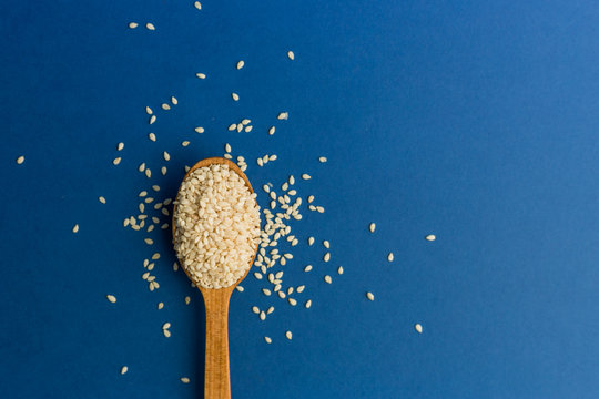 White sesame seeds in spoon on blue background. Color of the year 2020. Healthy food and drink concept. Copy space background. Flat lay style. Top view.