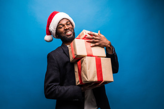 Young African American man wearing a santa hat holding presents , isolated on blue background