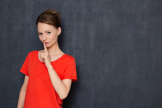 Portrait of flirty young woman smiling and showing silence sign