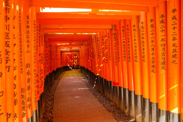 Kyoto, Japan - April 28, 2017: Fushimi Inari Taisha is the most important Shinto shrine famous for its thousands of red torii gates.The lettering engraved on pole are the name of donated organizations