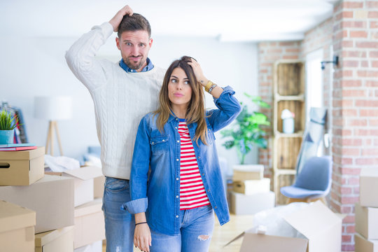 Young beautiful couple standing at new home around cardboard boxes confuse and wonder about question. Uncertain with doubt, thinking with hand on head. Pensive concept.