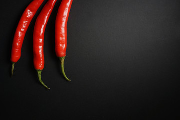 Canvas Prints Hot chili peppers Top view stalk of red hot chili pepper over black background.
