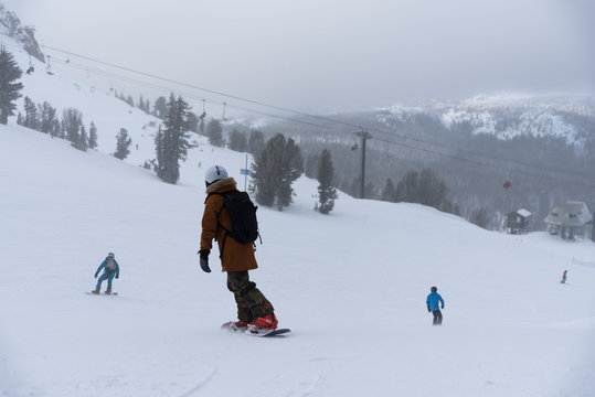 snowboarder enjoying skiing in mountains in the evening on the slope at winter ski resort Mammoth Lakes