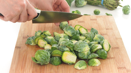 Poster Brussels Brussels sprouts. Woman cuts fresh organic Brussels sprouts on a wooden cutting board, close up on white background