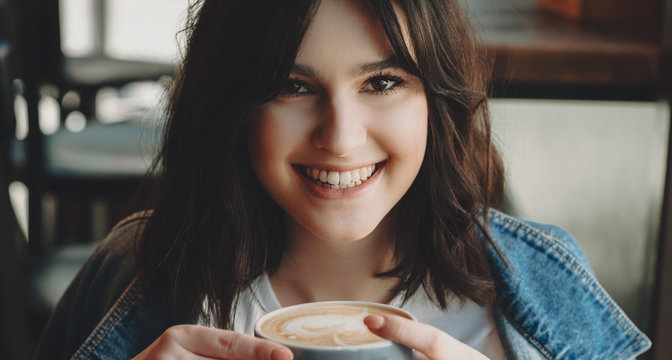 Close up portrait of a charming young woman looking at camera laughing while drinking a coffee in a coffee shop after work.