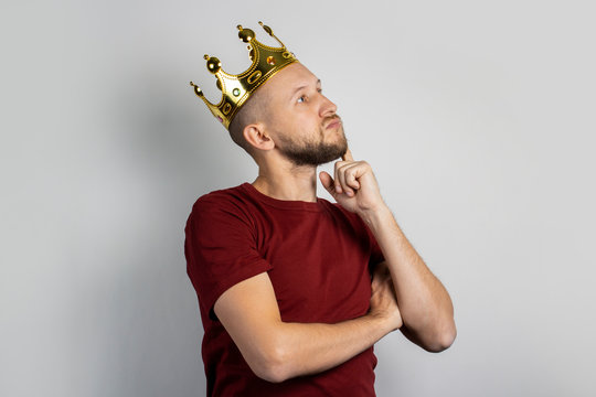 Young man with a crown on his head on a light background. Concept is king, luck, gain, rich, dream, goal, aspiration. Banner