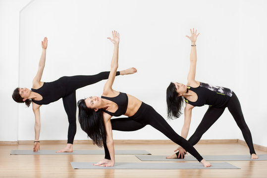 Beautiful slender women in black sportswear standing in different yoga poses, leaning towards in one direction, lifting one arm up. Group yoga classes. White background. Useful pastime concept