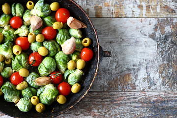 Photo sur Toile Bruxelles Brussels sprouts with vegetables and herbs in a pan. Cooking Brussels sprouts. Vega food. Selective focus.