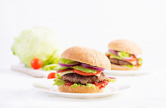 Big sandwich - hamburger burger with beef, avocado, tomato and red onions on light background. American cuisine. Fast Food