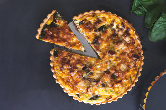 freshly bake  leek bacon spinach quiche on dark blue background with copy space, vertical,  top view